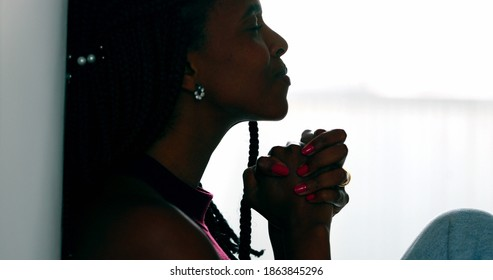Hopeful woman praying that life will get better. Black African female prayer