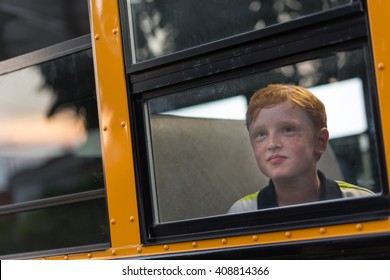 Hopeful young boy looking out school bus window
