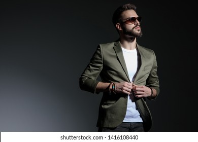 Hopeful young man closing his green jacket's buttons and looking to the side while wearing sunglasses and white t-shirt, standing on gray studio background