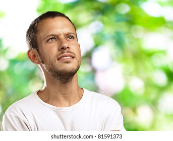 hopeful young man thinking about his future against a park background