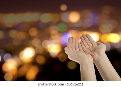 Hopefully beseeching cupped female hands held  against colorful lights background