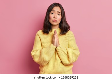 Hopeless brunette woman keeps palms pressed together and looks with imploring expression begs for favor asks to give one more chance wears long sleeved yellow jumper isolated over pink wall.
