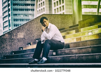Hopeless depressed businessman sitting at stairway outdoor. Bankrupt businessman sitting outdoor. Stressed and Unsuccessful business and financial stock market trading concept.Dark toned