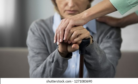 Hopeless female retiree sitting on sofa young nurse touching her hands carefully