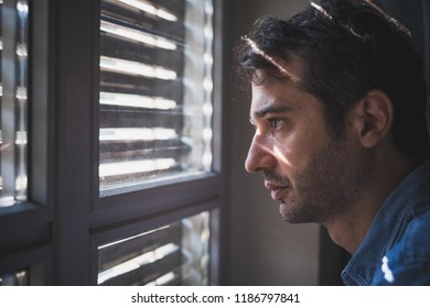 Hopeless man feeling alone and lost looking out window