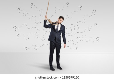 Hopeless young businessman trying to suicide with question signs concept