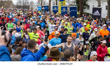 HOPKINTON, USA - APRIL 20: Athletes competing in the Boston Marathon 2015 a few minutes after the start of the competition in Hopkinton, MA, USA with lots of locals cheering them up on April 20, 2015.