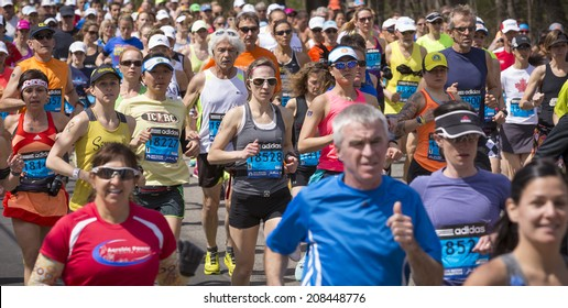 HOPKINTON, USA - APRIL 21: Amateur athletes heading from Hopkinton to Boston fast and steadily a few minutes after the start of the Boston Marathon 2014 on April 21, 2014.