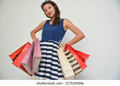 hopping woman holding shopping bags on white background at copy space. Beautiful young mixed race Caucasian