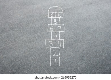 Hopscotch game being drawn with a chalk on the asphalt ground as seen from above