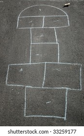Hopscotch game outline drawn in chalk on driveway