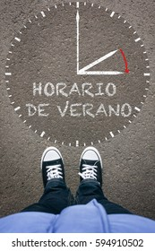 Horario de Verano, Spanish Daylight Saving Time clock with pair of legs and shoes on asphalt ground, high angle footsie or flortrait, personal pespective from above.