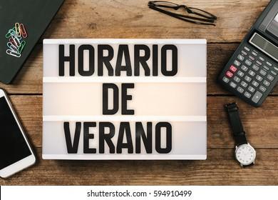 Horario de Verano, Spanish Horario de Verao, Portuguese Daylight Saving Time in vintage style light box on office desktop, high angle birds eye view