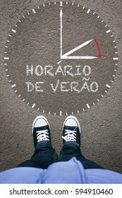 Horario de Verao, Portuguese Daylight Saving Time clock with pair of legs and shoes on asphalt ground, high angle footsie or flortrait, personal pespective from above.
