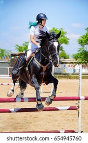 HORCHE, SPAIN - MAY 31, 2017: Woman doing jumping exercise with horse on a sunny day