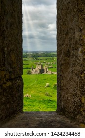 Hore Abbey is an atmospheric stone remains of a 13th-century Cistercian monstery, taken from the Rock of Cashel with walkers on the trail and sun rays braking through the clouds Co. Tipperary, Ireland
