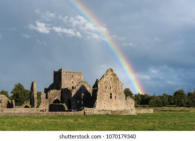 Hore Abbey under a rainbow and dark, rainclouds. The Abbey is a ruined cistercian monastery near the Rock of Cashel in County Tipperary, Republic of Ireland.