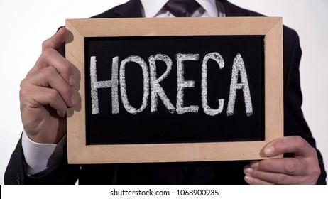 HoReCa written on blackboard in businessman hands, catering service industry, stock footage