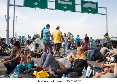 Horgos, Serbia - September 16, 2015: Refugees wait on a highway at the border between Serbia and Hungary.