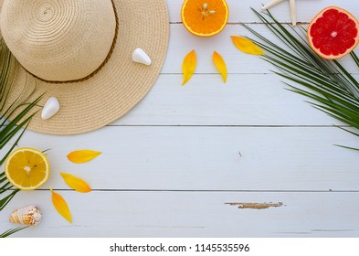 horisontal frame from fruits, hat, tropical palm leaves, seastones on white wooden background. Summer concept. Flat lay, top view, copy space mock up.