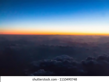 Horizon line of orange sky. Flight over clouds at beautiful golden orange sunset time or light sunrise.