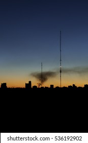 Horizon sunset with buildings silhouette and two tall antennas. The smoke covers the sky from left to right