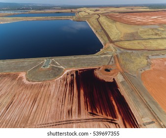Horizontal Aerial View Of Red Tailing Ponds With Various Colors Shapes And Textures On A Sunny