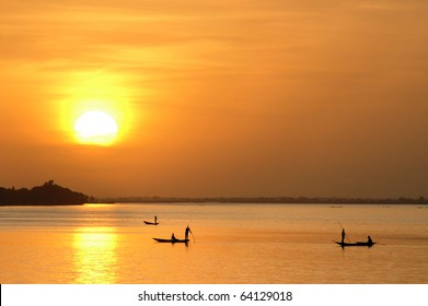 Horizontal of African fishermen in canoes at sunset
