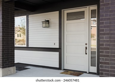 Horizontal Angled Shot of White And Black Front Entryway with White Siding, a White Front Door, and Black Framing