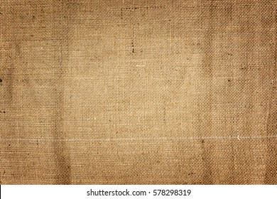 Horizontal background of burlap with white seam. Background of natural brown cloth. darkening of the edges