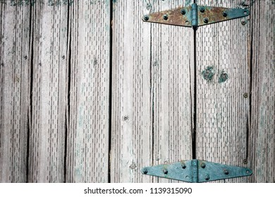 horizontal background image of rustic wood planks surface with peeling blue painted metal door hinges great for lots of copy space.