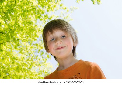 Horizontal backlit portrait of blond boy in a sunny day