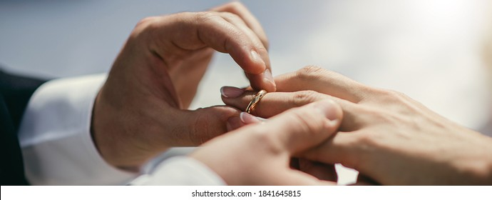 Horizontal banner bride and groom holding hands. Closeup couple exchanges wedding rings during ceremony. Wedding, union, loyalty concept.
