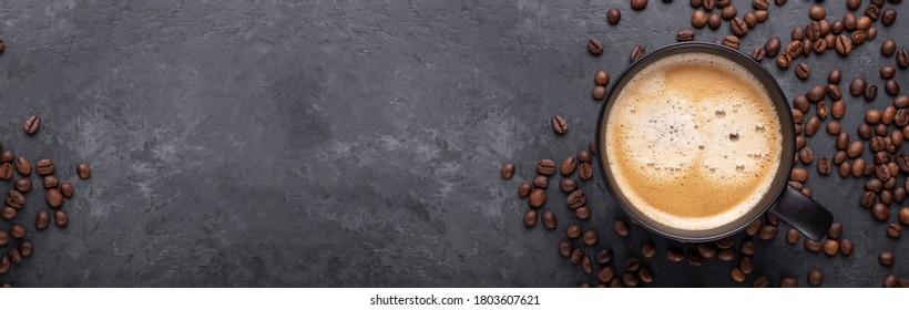 Horizontal banner with cup of coffee and coffee beans on dark stone background. Top view. Copy space - Image - Shutterstock ID 1803607621