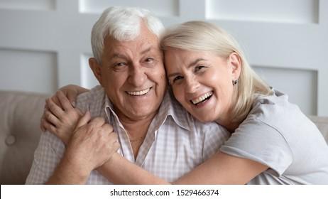 ソファに座った恋愛の横断幕の幸せな老夫婦が抱きしめ、笑う白髪の夫と妻がカメラを見てポーズを取る、年配の家族のポートレート、長生きの結婚、誠実な感情コンセプ