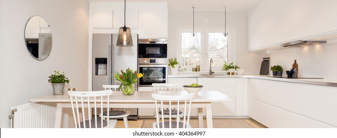 horizontal banner of a kitchen interior with table and white cupboards