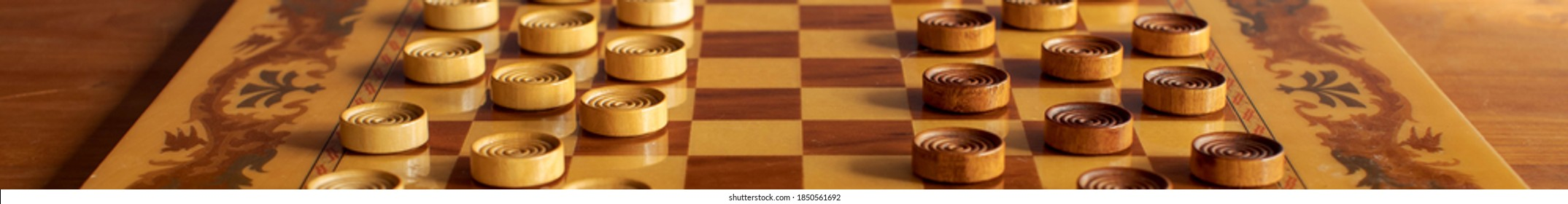 Horizontal Banner of a Vintage wooden checkerboard with brown and cream colored checkers.