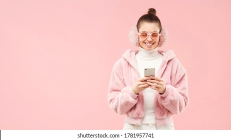 Horizontal banner of young girl in winter coat, ear warmers and glasses, reading messages on phone screen, isolated on pink background, copy space on left