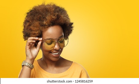 Horizontal banner of young smiling dark skin african american woman in golden glasses, isolated on yellow background