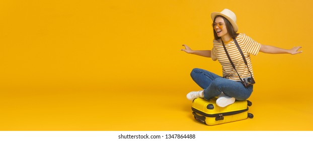 Horizontal banner of young tourist girl sitting on suitcase, pretending flying on a plane, isolated on yellow background with copy space. Dreams about traveling concept