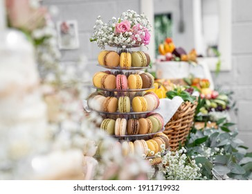 Horizontal beautiful macaron cake patisserie multi tier stand full of macarons all flavours colours real wedding with flowers and roses pink strawberry yellow brown chocolate cookies pyramid tower