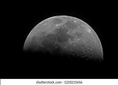 Horizontal big and bright Moon in its first quarter phase, isolated in dark background into space, taken by telescope.