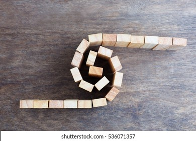 An horizontal bird's eye view photographic  image of two converging lines of wood blocks forming a swirl in order to illustrate yin-yang and balance.