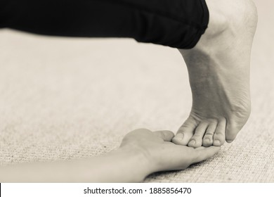 Horizontal black and white detail of yogini wearing long dark yoga pants making backward bending exercise on floor, reaching foot and touching toes with open hand. Indoor home yoga practice in sepia