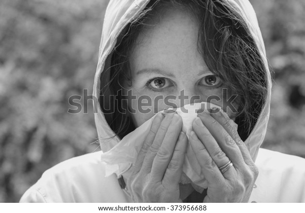 horizontal black and white image close up of a single woman outside with a hooded jacket on blowing her nose with tissues and shallow depth of field / Spring Allergies and Illness