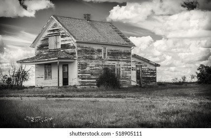 horizontal black and white image of an old rustic abandoned house with a veranda sitting under a cloudy sky.