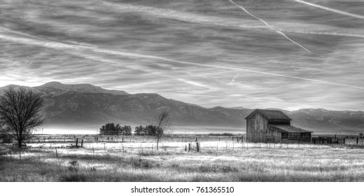 Horizontal Black and White Image of an Old Barn, Trees, Meadow and Mountains at Sunrise.
