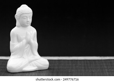 Horizontal black and white shot of a white figure in meditation pose
