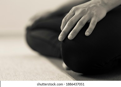 Horizontal black and white side detail of yogini on the floor with legs crossed in lotus pose. Woman indoors wearing black yoga pants with hands resting on knees. Home yoga practice in sepia tone