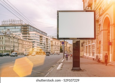 Horizontal blank billboard on the city street. In the background buildings and road with cars. Film effect. Mock up.